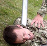 Agonised soldier pinned by aluminium baseball bat